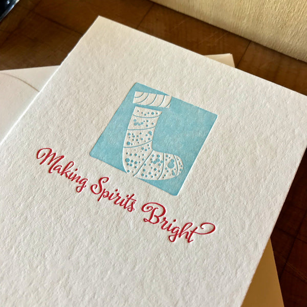 closeup of making spirits bright letterpress holiday card in red pepper and sky blue