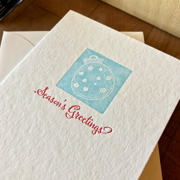 closeup of seasons greetings letterpress holiday card in red pepper and sky blue