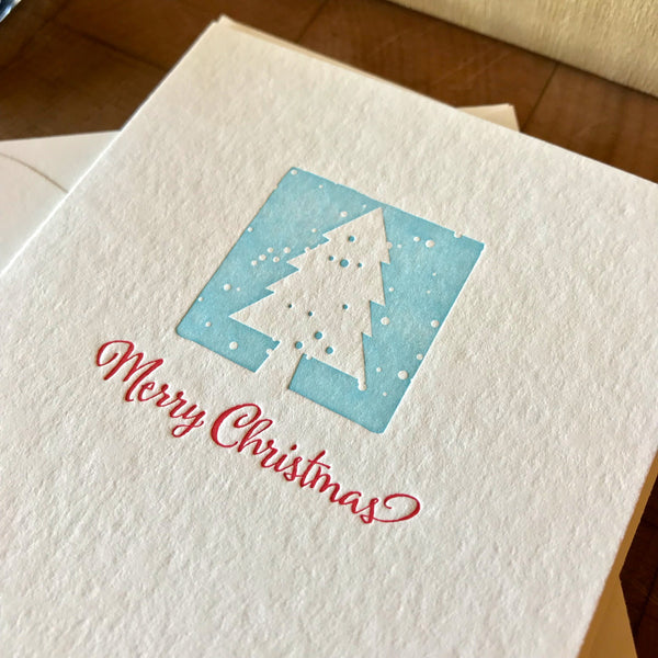 closeup of merry christmas letterpress holiday card in red pepper and sky blue