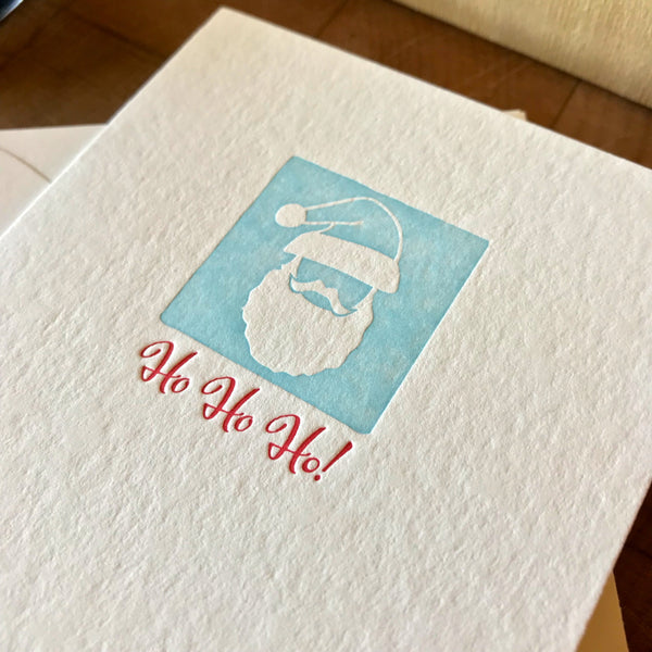 closeup of ho ho ho letterpress holiday card in red pepper and sky blue