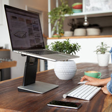 Girl using a Classic Silver Tiny Tower Stand in a trendy cafe. Her setup includes a matching Macbook Pro, keyboard and mouse