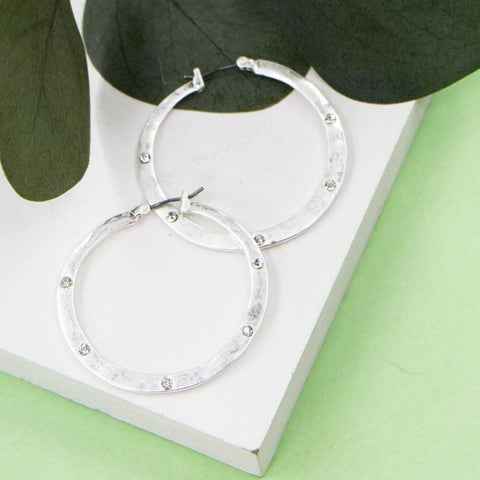 WORN SILVER HOOP EARRINGS WITH CRYSTALS