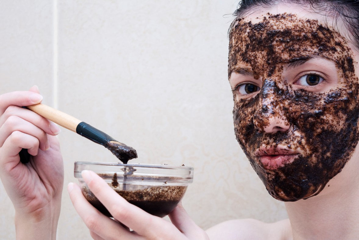 young woman applying facial scrub on her face