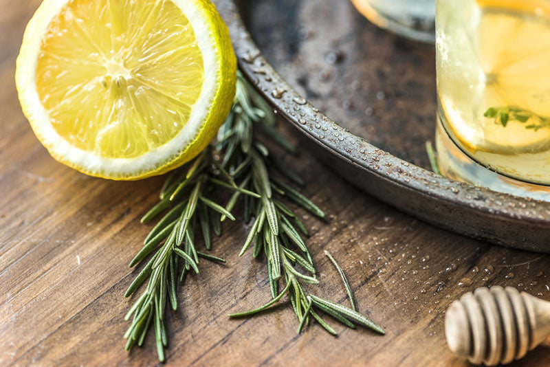 Composition of half lemon, rosemary and glass of lemonade