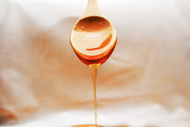 Honey flowing down of the wooden spoon