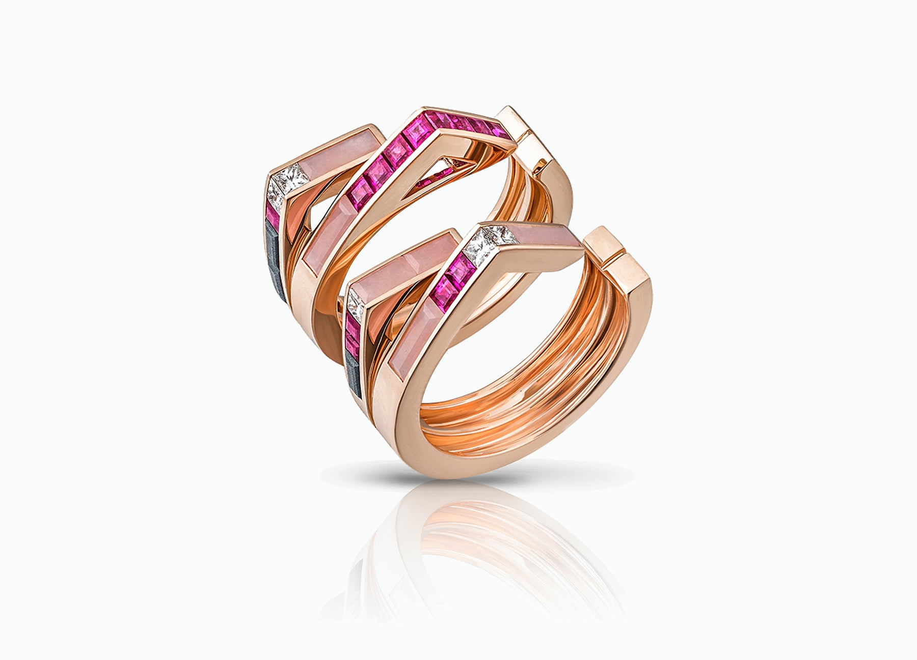 Stellar Pair of Stacking rings in 18K rose gold set with rubies and diamonds and pink opal by Tomasz Donocik Seen apart three quarter view