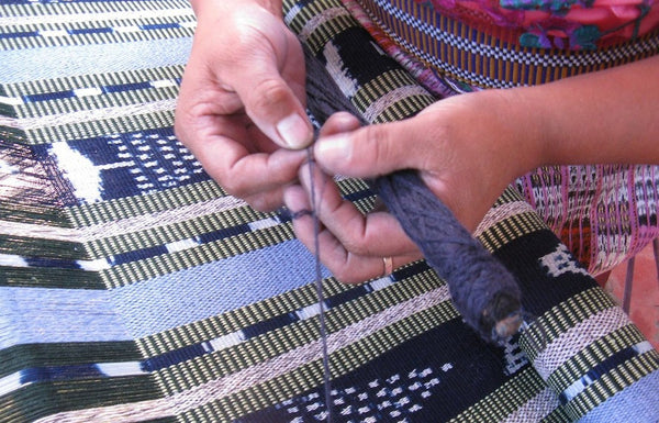 Hands of Master Weaver María Florinda Pérez with backstrap loom shuttle over a nearly finished rebozo