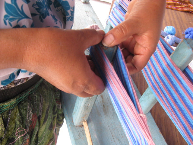 Close up of hands removing the blue and pink warp threads from the urdidor