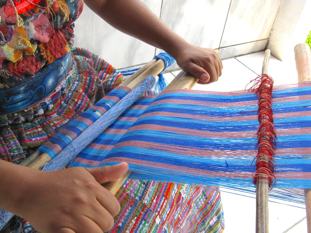 Close up of working area of backstrap loom and hands packing the weft threads with beater