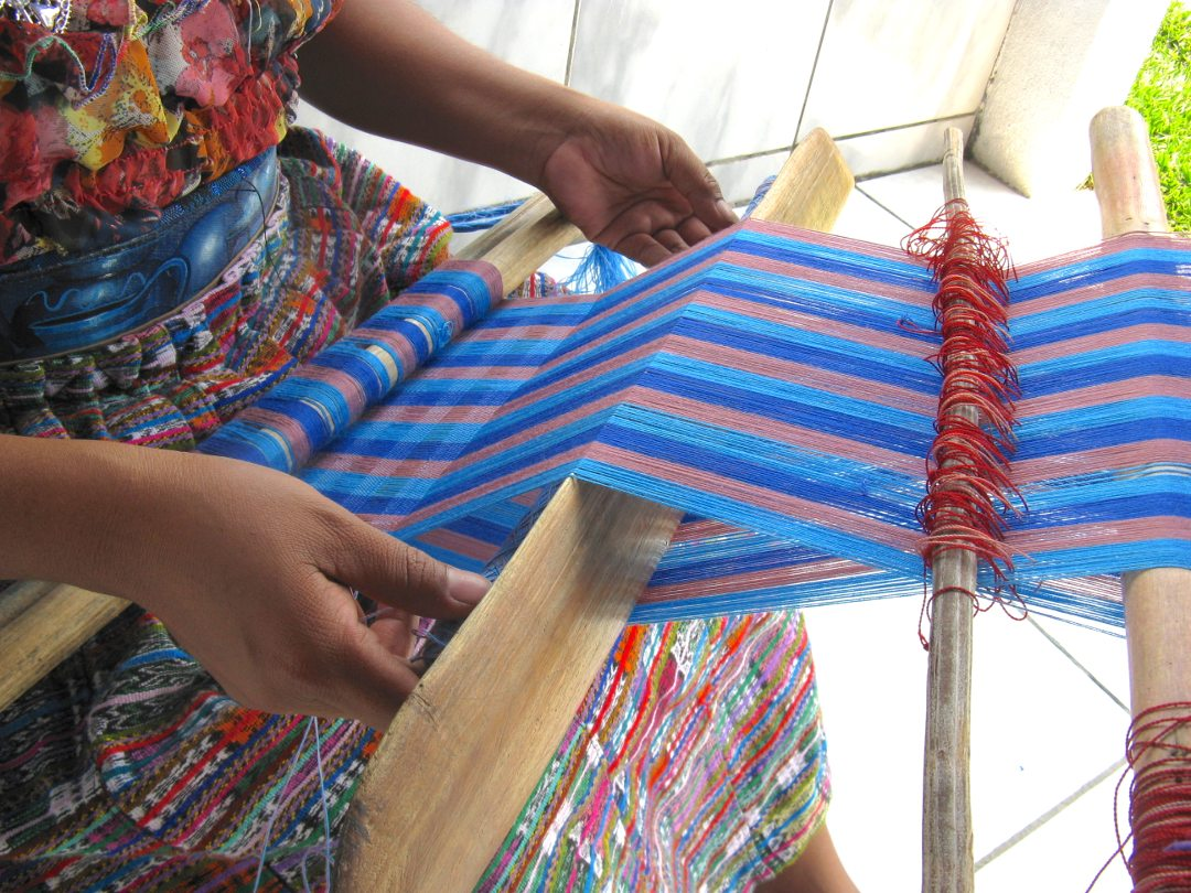 Close up of the working area of a backstrap loom and hands passing the shuttle through the weft