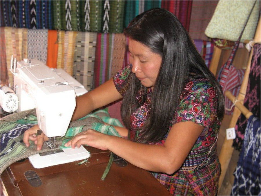 Cristina Cumes, Guatemalan Apparel Designer and Coordinator of Women's Backstrap Loom Weaving Cooperative sewing an apron