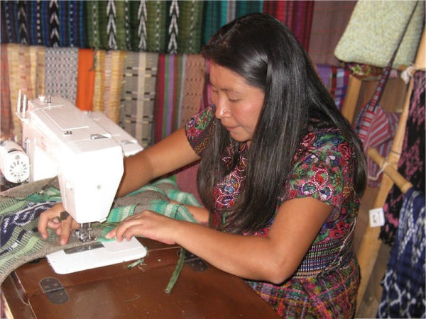 Cristina Cumes Coordinator of Quetzalli Women's Weaving Cooperative Sewing an apron from backstrap loom woven fabric