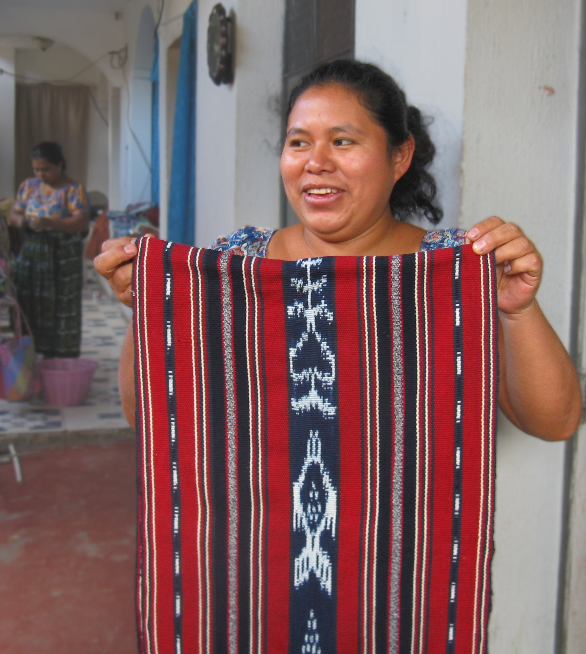 Mayan Master weaver Isabel Pérez Mendoza holding one panel of a backstrap loom woven bedspread
