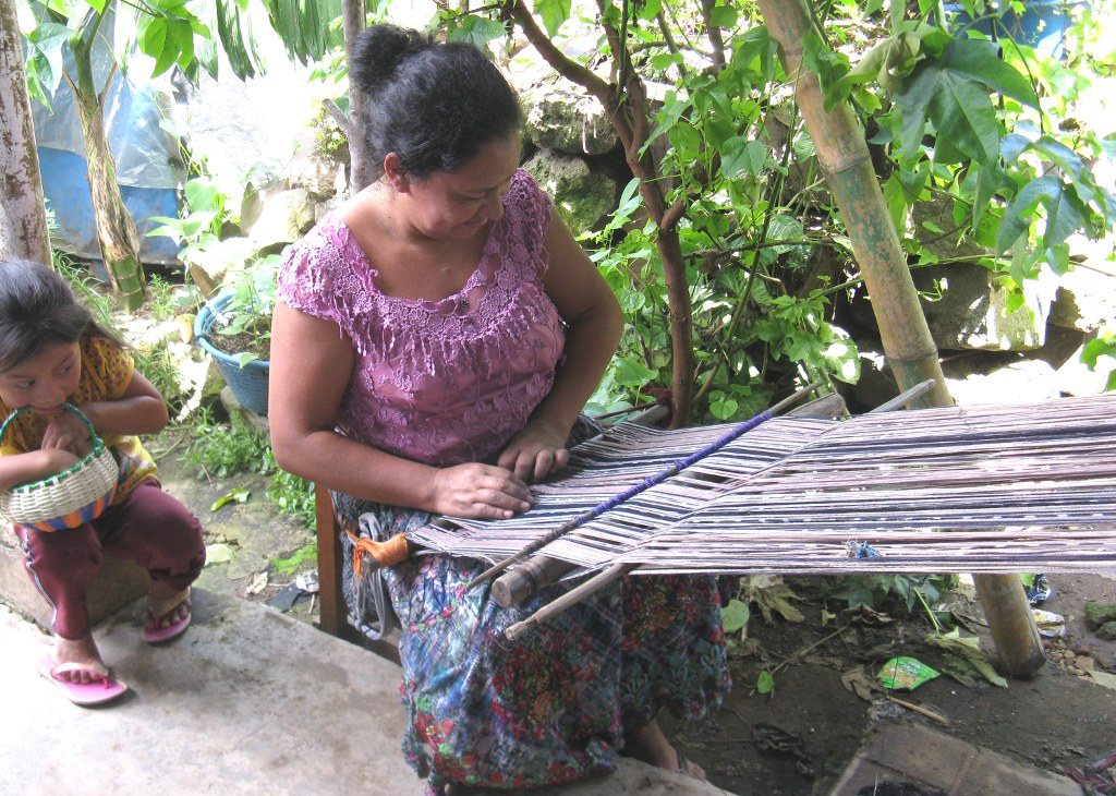 Master Weaver María Carmen Pérez from Guatemala adjusting the backstrap loom to begin a new bedspread