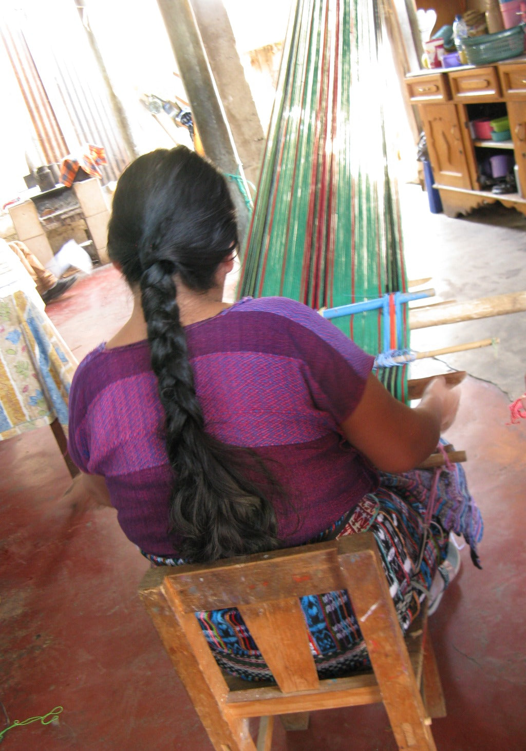 Master Weaver Natalia Mendoza from guatemala seated at the longest possible backstrap loom set up backview