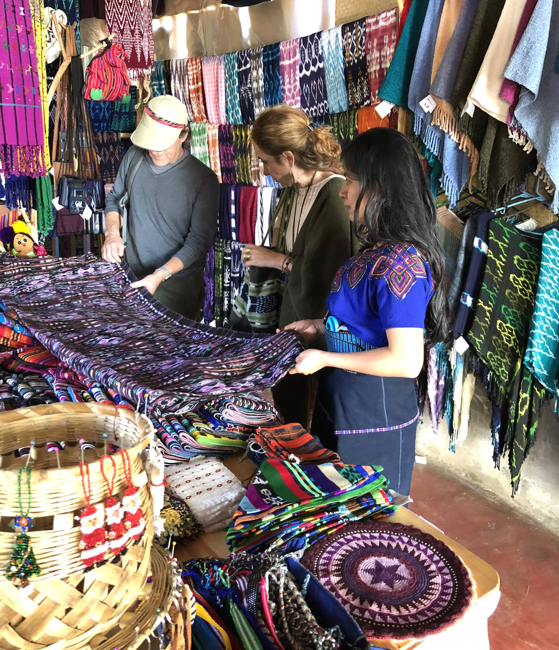 Mayan backstrap loom weaver Amelia Vásquez attending to customers at the weaving cooperative