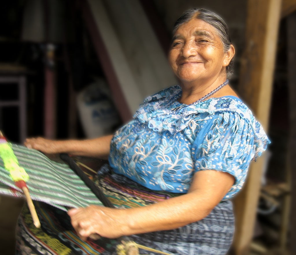 The indomitable 80 year old Naan Chaya Méndez seated at her backstrap loom with a big grin