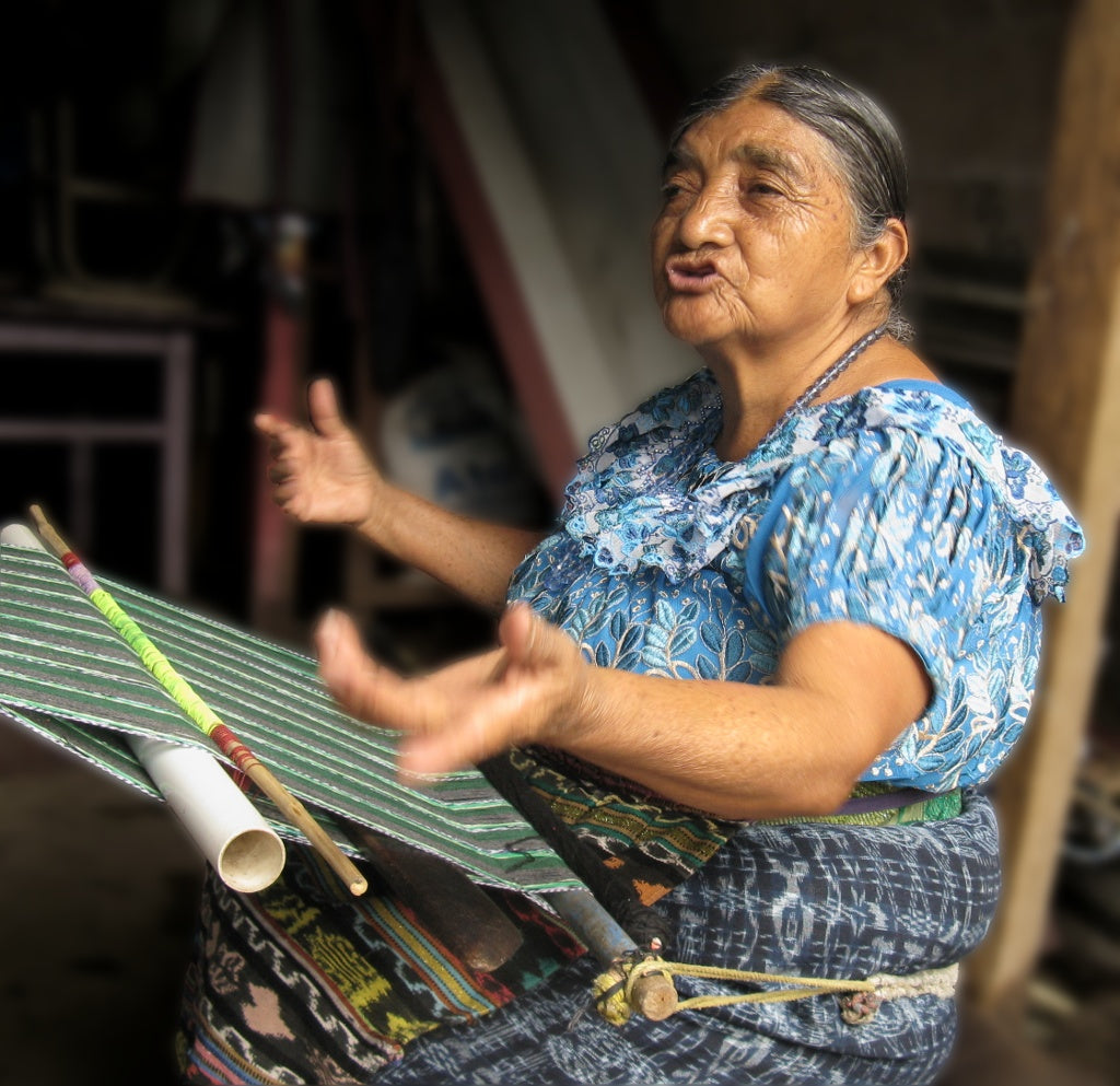 Master  Weaver Naan Chaya Méndez seated at her loom expounding on the price of a weaving 72 years ago 1