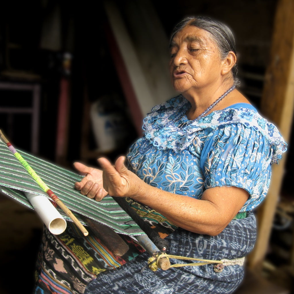 Master  Weaver Naan Chaya Méndez seated at her loom talking about the price of backstrap loom weaving from long ago