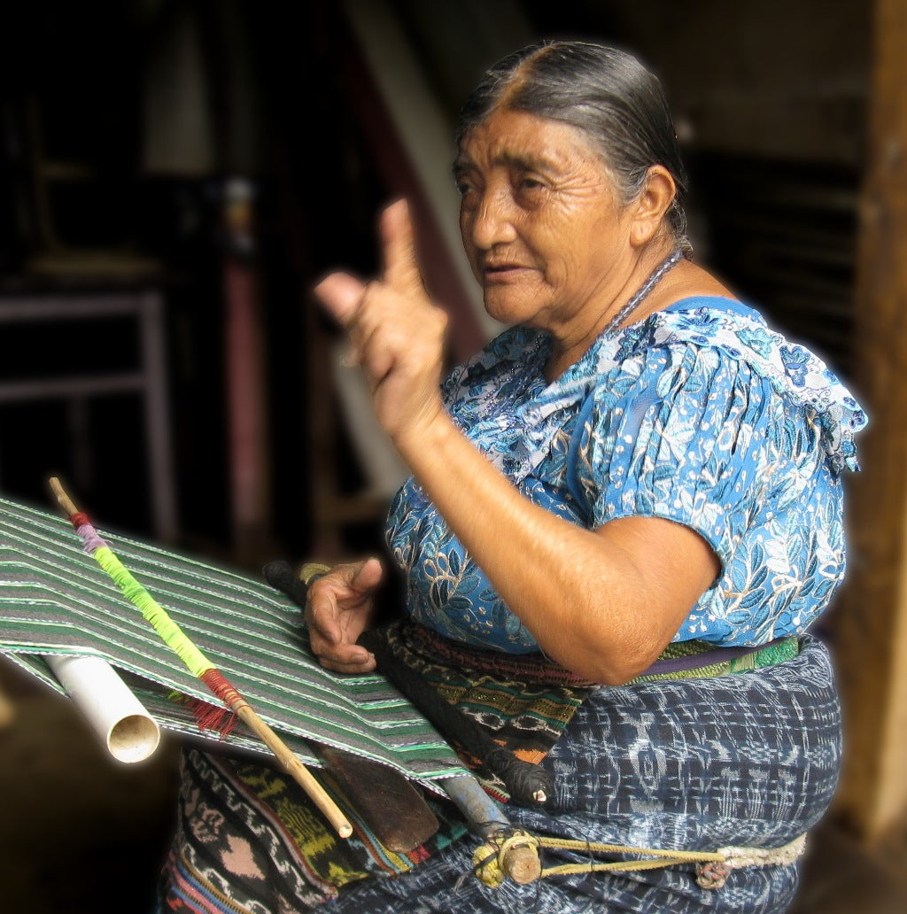 Naan Chaya Méndez seated at her loom discussing the the price of a weaving then and now