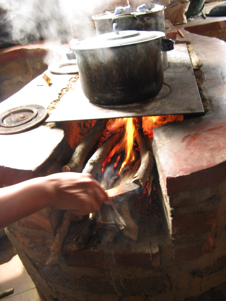 Feeding wood into a smoking hot wood fired stove boiling water ready for dye plants