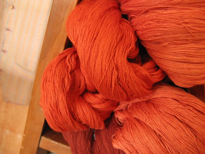 orange colored cotton thread dyed with carrots ready to be woven on a backstrap loom