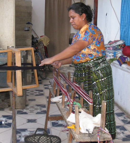 Artist Florinda Pérez winding warp threads on an urdidor preparing to set up a backstrap loom