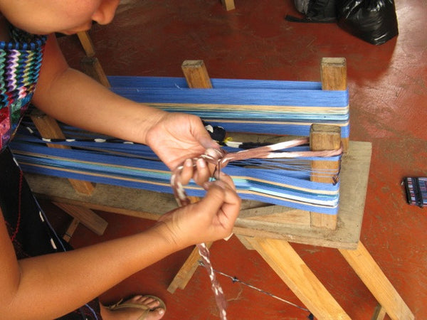 Hands inserting a finished jaspe (ikat) labore onto the warping board within the other warp threads
