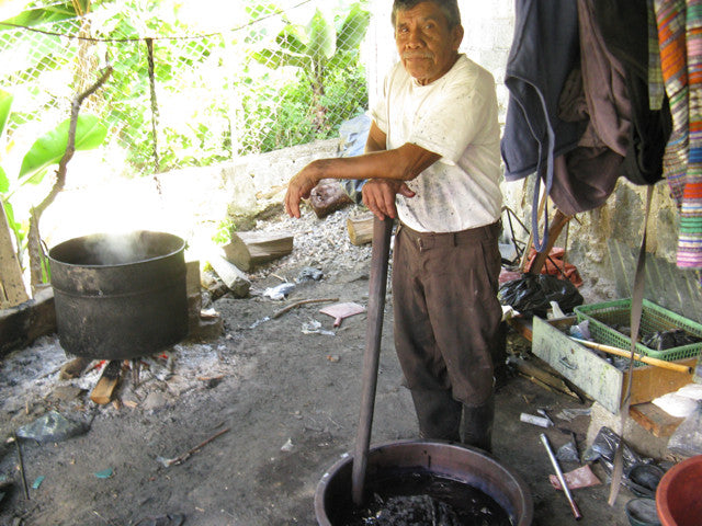 Esteban Mendoza leaning on a stick in his indigo ikat dying area open fire with large pots