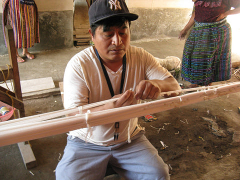 Oscar Mendoza seated between stretched out labores tightly wrapping ikat (or jaspe) designs