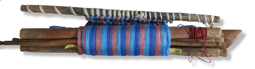 Rolled up backstrap loom with a blue and pink in-process weaving showing the loom's portability