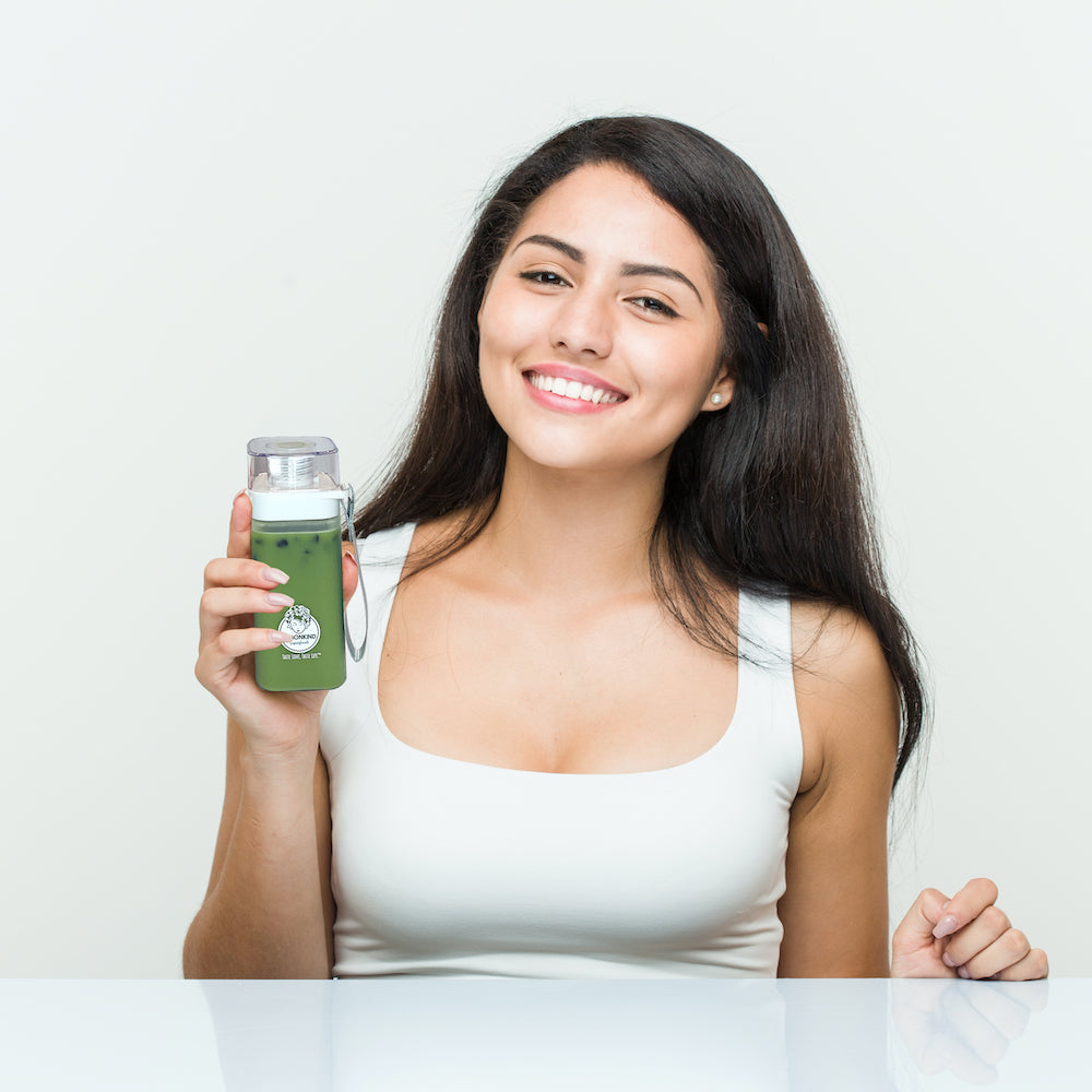 woman holding a NUTRIBOBA ceremonial matcha moringa tea latte