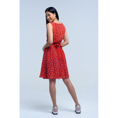 Sleeveless red dress with geometric pattern and bow. Details of folds in the back. Round neck. Loop detail on the waist. Side zipper closure. Fresh fabric with ruffles.