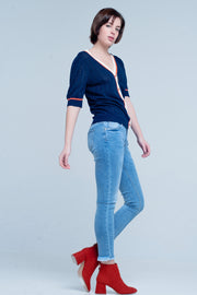 Blue medium washed skinny jeans with ripped ankles is made of strong cotton with a little stretch. The denim pants has five functional pockets and a zipper and button closure.