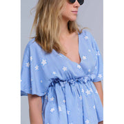 Blue crop top with V-neck and short sleeves. It has an elastic band ith ruffles under the chest. It is a stripes top whit stars printed pattern.