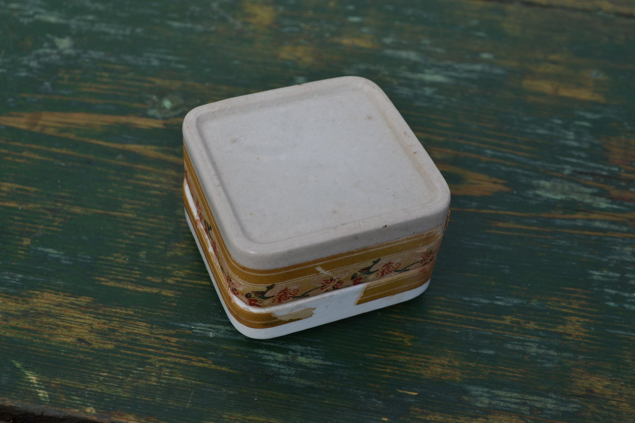 An opened white rose tooth paste pot with original contents and paper seal