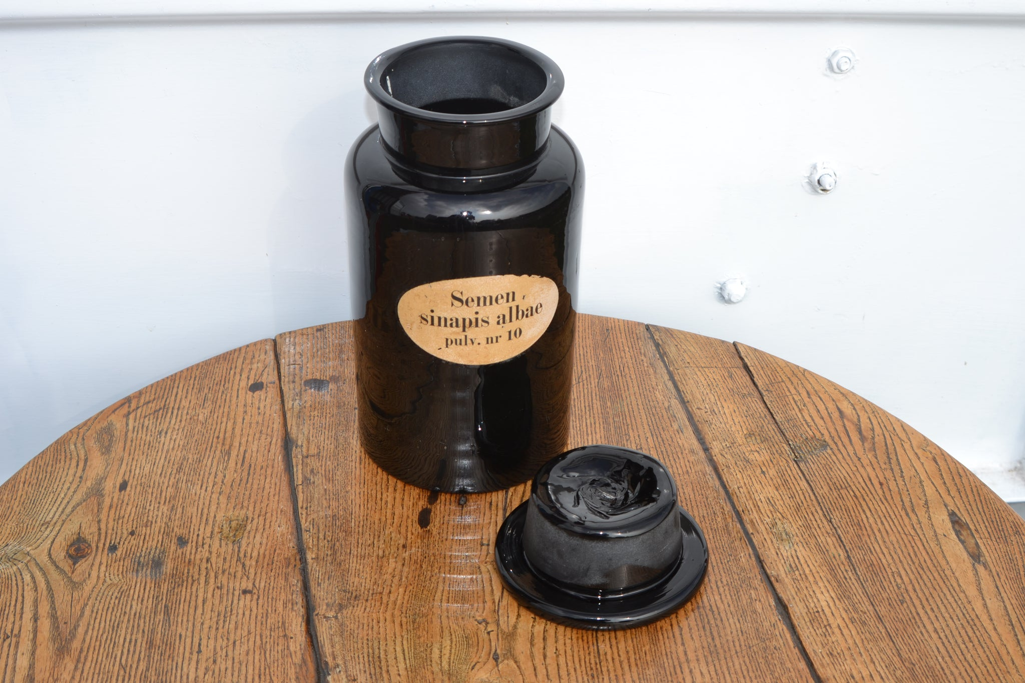 A Georgian black glass chemist jar with original Semen Sinapis albae label