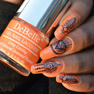 8ml bottle of pastel orange nail lacquer by DeBelle held by a hand adorned with orange nail art