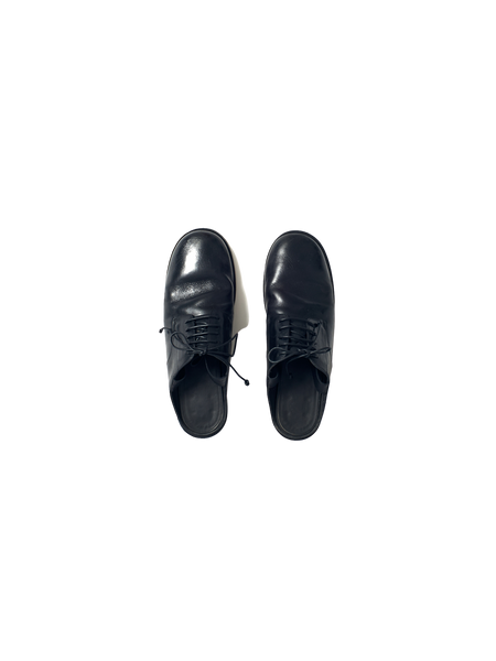 black leather oxford shoe with open back and ribbon tie at the ankle