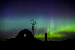 A display of the Aurora Borealis behind an old barn at a homestead on the Saskatchewan Prairies