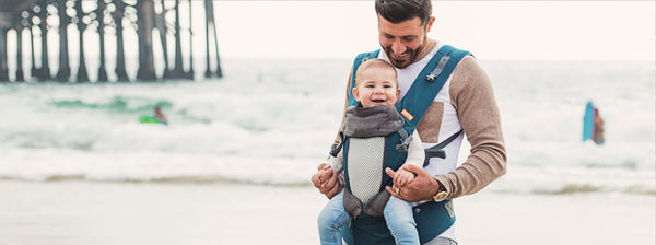Dad at the beach wearing his child in the Beco 8 baby carrier