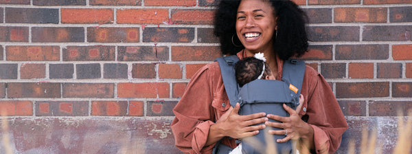 Smiling woman wearing her newborn in Beco Gemini baby carrier