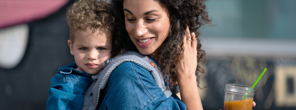 Smiling mother carrying her toddler on her back using the Beco Toddler baby carrier
