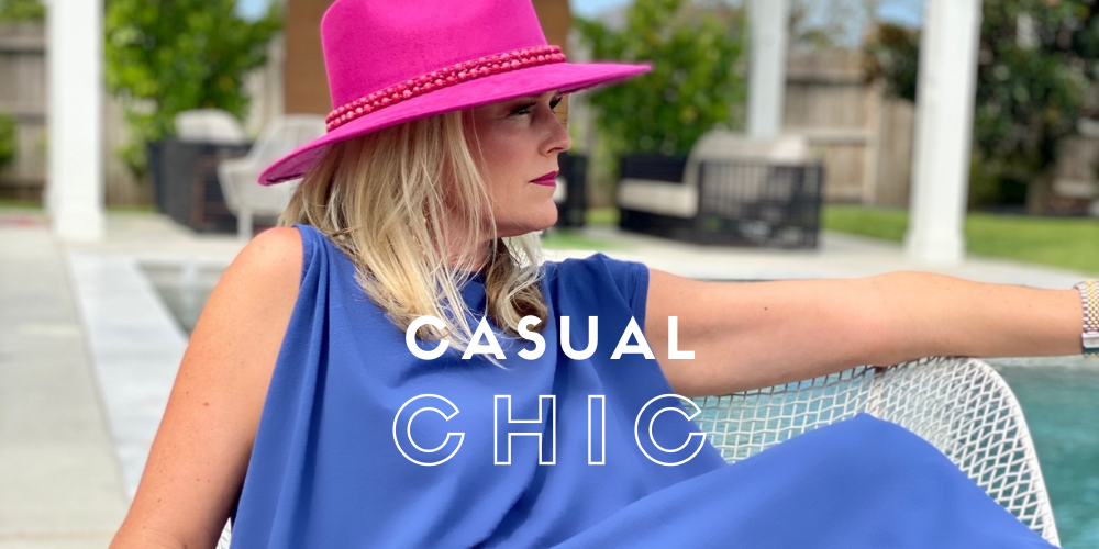 women posing by the pool wearing a navy dress and pink hat, casual chic description text
