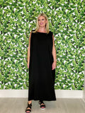 Photo of a women wearing a black house dress looking satisfied