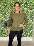 Women holding a yoga mat wearing an olive green tori top