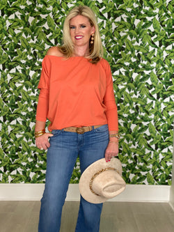 Women wearing a orange tori top looking happy off the shoulder long sleeve top