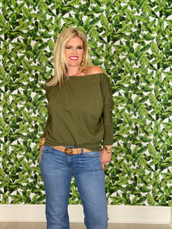 Women wearing a olive green off the shoulder tori top