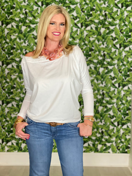 Women wearing a white tori top off the shoulder long sleeve top