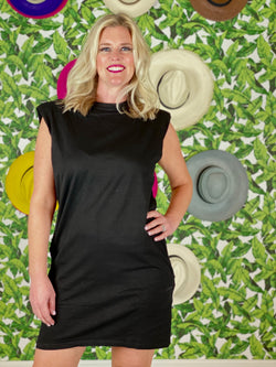woman standing with hand on her hip wear a short black cotton dress with shoulder pads